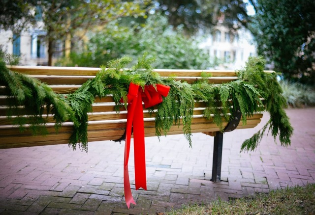 Red bow tied on garland on a park bench.