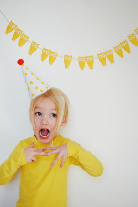Little girl with birthday hat and owl garland.