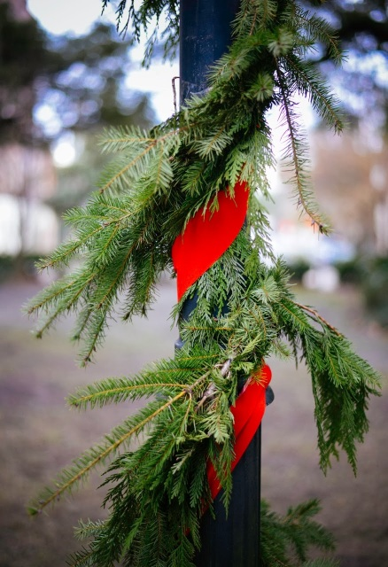 Red ribbon and greenery on pole.