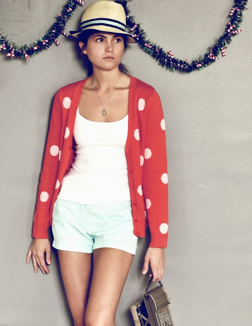 Model with a red and white polka dot sweat on, with a hat and Christmas garland hanging behind her.