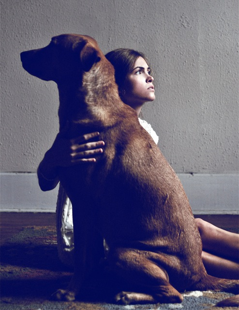 Model posing with very large brown dog for a style spread.