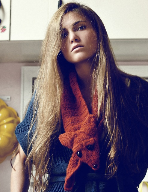 Model with messy hair and a fox scarf on for a style spread.
