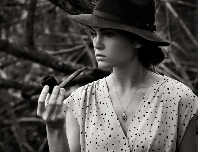 Model wearing a hat and smoking a pipe while in deep thought.